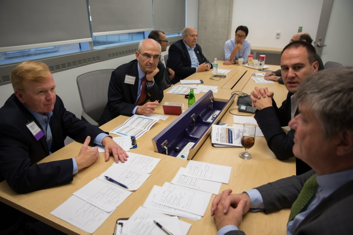 5 judges and 3 TCO personnel sitting at a table while judges deliberate on the 2015 Innovation Competition contestants.
