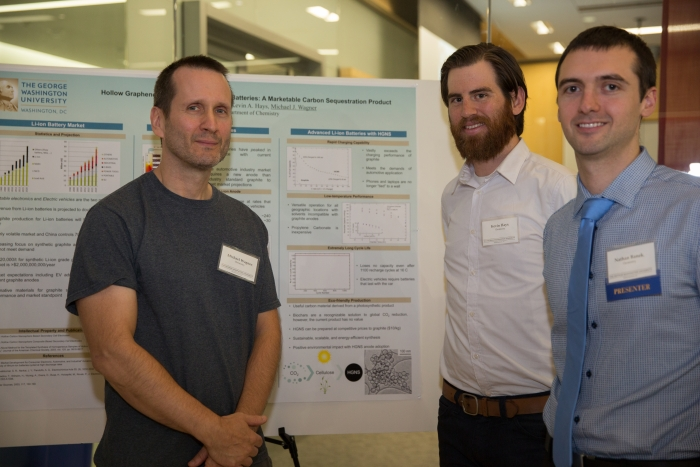 Three-person physical science team that won first place standing next to their poster.